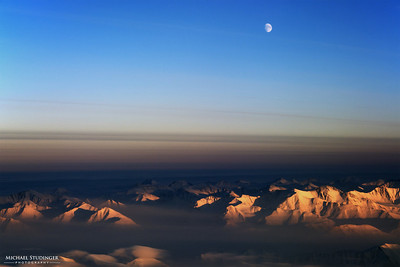 The moon over northeast Greenland and typical arctic fog banks seen from the NASA P-3 research aircraft while descending into the survery area over sea ice north of the Fram Strait.